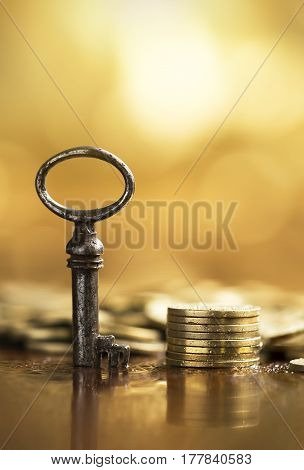 Business success concept - key and golden money coins in vertical