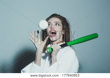young pretty woman or cute sexy girl with beautiful long hair and red lips on adorable surprised happy face in fashionable white shirt holds green baseball bat or racket and ball on grey background