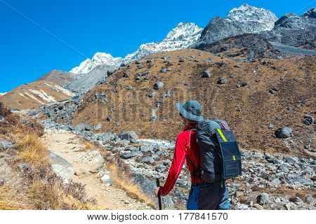Mountain Hiker walking on Footpath in Nepal high altitude trekking carrying Backpack with Solar Panel attached for charging Battery of mobile Telephone