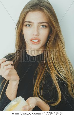 Pretty girl or beautiful woman with young face skin and long blond hair putting gel or balm on sexy lips from jar on white wall. Cosmetology beauty and spa