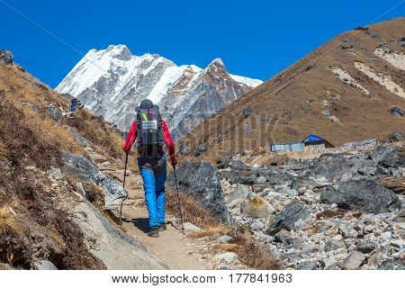 Mountain Climber walking on Footpath in Nepal trekking carrying Backpack with Solar Panel attached for charging Battery of mobile Telephone snowy high altitude Summits and Peaks on Background.