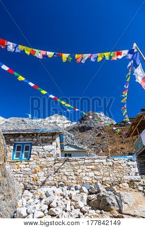 Stone Buildings of Mountain Village at high altitude area of Nepal Mountains with traditional Buddhist Prayer Flags against blue Sky
