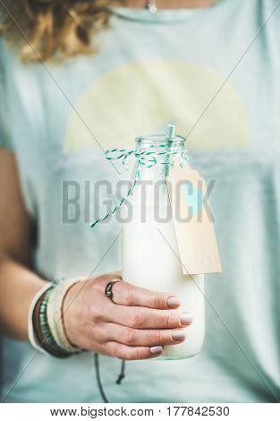 Young blond woman in t-shirt holding bottle of dairy-free almond milk in her hand. Clean eating, vegan, vegetarian, dieting, healthy food concept