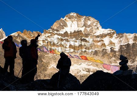 Silhouettes of Mountain Climbers planning next Day ascent staying on rocky place in front of high Summit illuminated by Evening Sunlight and traditional Buddhist Prayer Flags in Nepal.