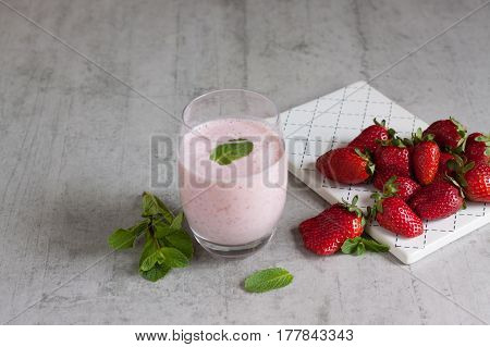 Strawberry smoothie in a transparent glass with strawberries on a white ceramic tray, on a concrete background