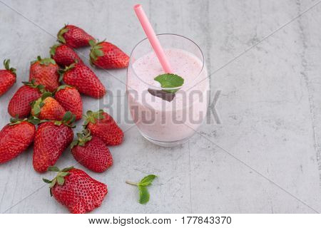 Strawberry smoothie in a transparent glass with a pink straw, on a concrete background with strawberries. Right copy space.