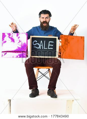 Bearded man long beard. Brutal caucasian angry hipster with moustache holding pink and orange shopping packages and sale inscription on blackboard sitting on chair isolated on white background