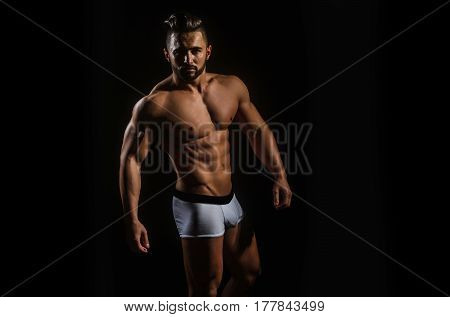 handsome muscular macho man or athlete guy with sexy body of bodybuilder with torso belly six packs has beard on serious face in white pants isolated on black background