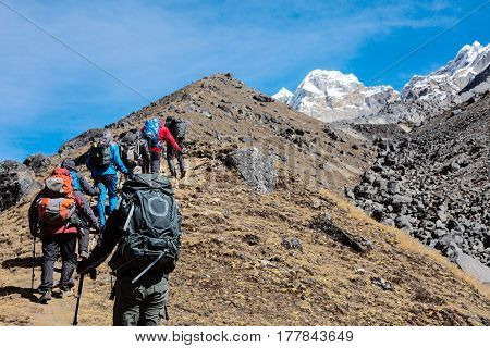 Members of Mountaineering Expedition moving up on yellow steep Slope towards high Altitude Mountains