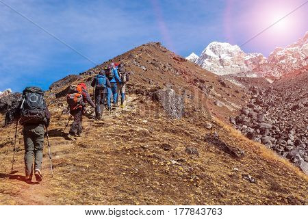Members of Mountaineering Expedition moving up on yellow steep Slope towards high Altitude Mountains with Sun shining