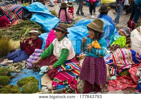 Cuzco Peru - December 25 2013: Woman and her chlidren in a street market at the Plaza de Armas in the city of Cuzco in Peru.