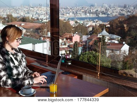 Business Woman working on portable Computer sitting at wooden Table of roof top Cafe next to large Windows with City View