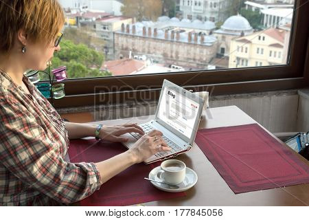 Person writing travel Notes on portable Computer at Roof Top Cafe sitting at wood Table next to Window with City View