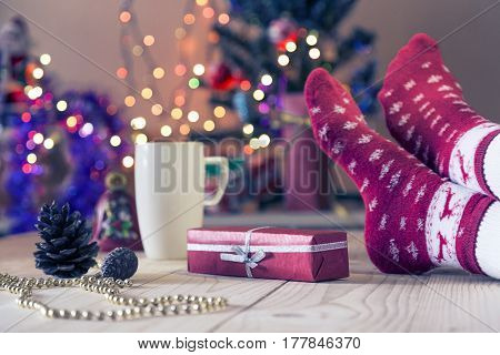 Christmas Eve Concept wooden floor with decorated gift package white mug and female foot in red socks with winter design. Christmas Tree and holidays illumination on Background toned colors