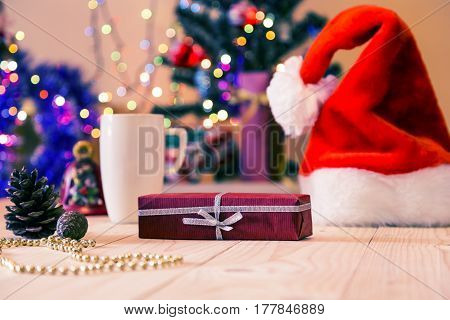 New Year gift and Santa Hat on wooden floor with blurred illuminated and decorated Christmas tree on background