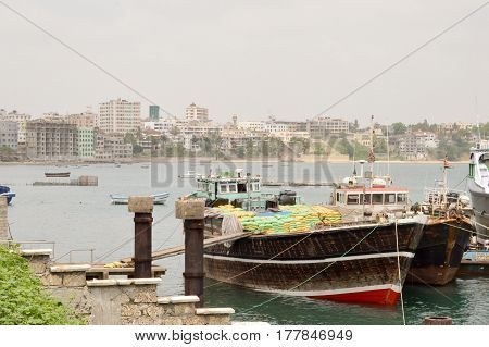 Boat loaded with bags in the port of Mombasa in Kenya with the city in the background