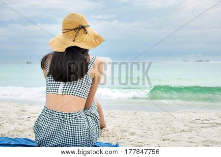 Girl Reading A Book On A Sandy Beach