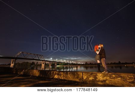 Loving couple standing against a background of the night sky. The girl with red hair and a guy with long hair standing on the background of the river. Man and woman hugging. Bridge on the River. Couple silhouette on background starry sky