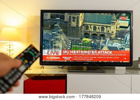 PARIS FRANCE - MARCH 22: Man holding remote control watching BBC channel reporting live scenes from Westminster Bridge after armed attack on March 22 in London. A police officer has been stabbed near to the British Parliament