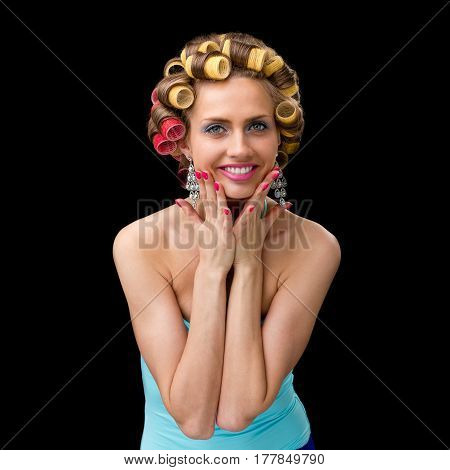 portarit of beautiful coquette young woman with curlers, isolated on black background