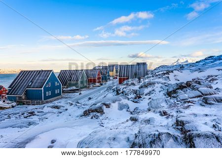 Yellow, Blue, Red And Green Inuit Houses Along The Snow Street With Rocky Landscape In Foreground An