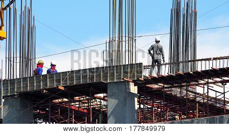 Engineer and workers on high building construction site and steel and cement texture and blue sky.