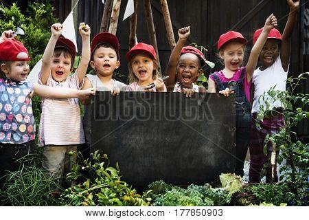 Group of children holding blank blackboard in garden