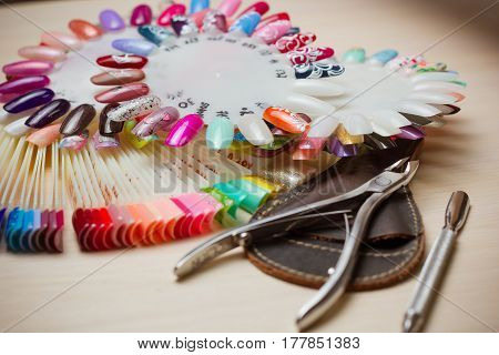 Table full of manicure utensils, manicure tools, nail polish colours on palette. Nails art accessories white.