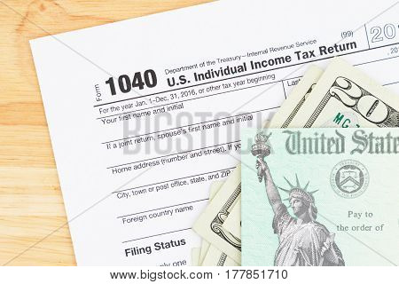 A US Federal tax 1040 income tax form with money and refund check on a wood desk