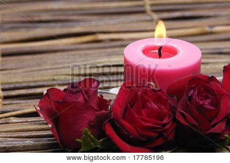 rote Kerze und rote Rose auf Bambusmatte