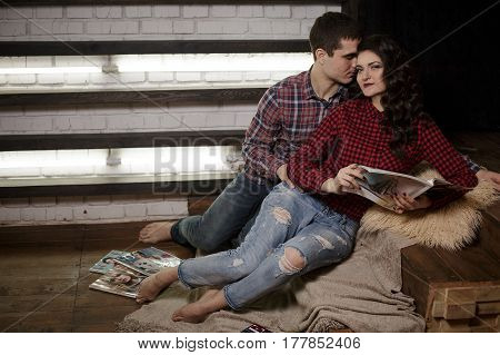 Man and woman on the bed. Man and woman hugging lay on the floor with warm blanket in bedroom and read interesting book together at sweet home. TRUE LOVE.