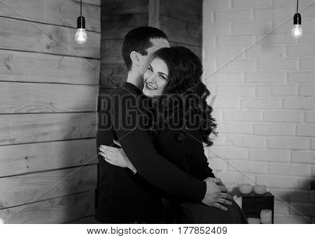 Man and woman are hugging. Happy woman hugging her husband. Happy couple at his new appartament. Black and white photo. Happiness concept.