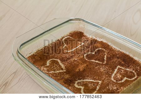 Valentines coffee cake with creamy souffle and savoiardi decorated hearts on beige wood.
