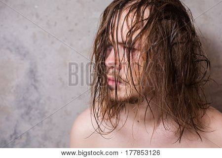 A man with a mustache and a beard with long wet hair on the background of gray walls copyspace. Wet beard