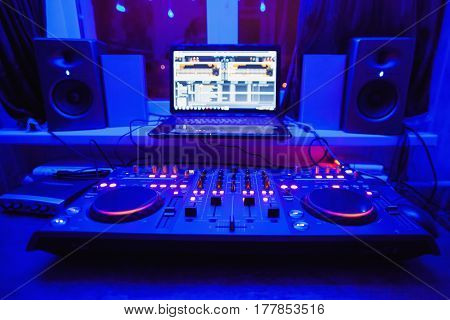 Music instrument. DJ console. Nout beech speakers stand on the windowsill. Blue light. Workplace of dj. Music concept