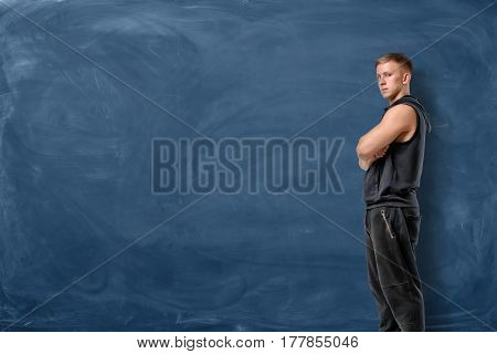 Muscular young man is standing his arms crossed and looking forward on blue chalkboard background. Sport and healthy lifestyle. Keep fit. Athletic body