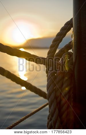 Detail Of Ropes On Sailboat With Sunset In Background
