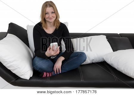 Smiling young woman is using her smart phone sitting cross-legged on a black and white couch with black and white pillows. Isolated on the white background. All potential trademarks and buttons on a smart phone are removed.