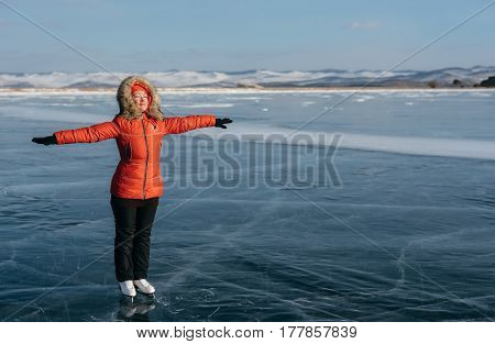 A girl on skates on the open ice on the lake enjoys the sunshine. The ice under your feet is very beautiful and thick, with cracks. The girl is sunbathing.