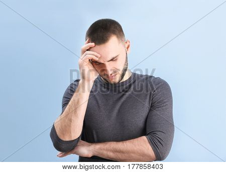 Handsome young man suffering from headache on color background