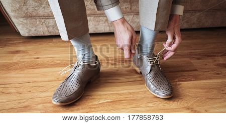 The man wears shoes. Tie the laces on the shoes. Men's style. Professions. To prepare for work to the meeting. Brown shoes