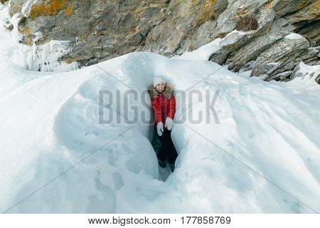 A woman is a tourist and a traveler in the ice of Lake Baikal. The girl is standing in a small gorge of ice and laughing. This gorge is the entrance to a small cave - the grotto. Location of the lake is Lake Baikal, Siberia, Russia.