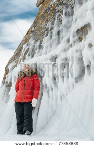 A woman is a tourist and a traveler in the ice of Lake Baikal. Girl standing on the rocky shore of the lake adorned with frozen waves. Location of the lake is Lake Baikal, Siberia, Russia.