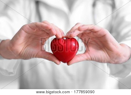 Female doctor with stethoscope holding heart closeup