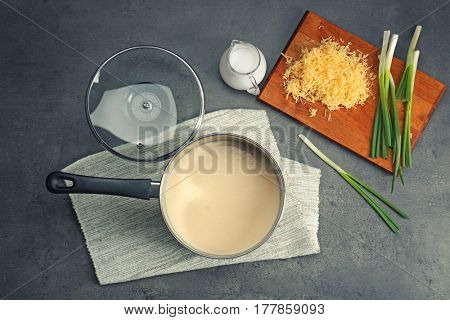 Saucepan with beer cheese dip and ingredients on table