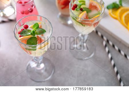Glasses of delicious wine spritzer on grey table