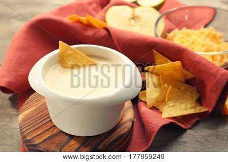 Bowl with beer cheese dip and nachos on wooden stand