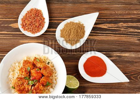 Plate with tasty chicken tikka masala, rice and spices on wooden table