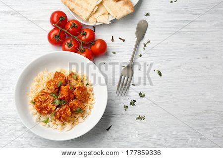 Plate with tasty chicken tikka masala and rice on wooden table