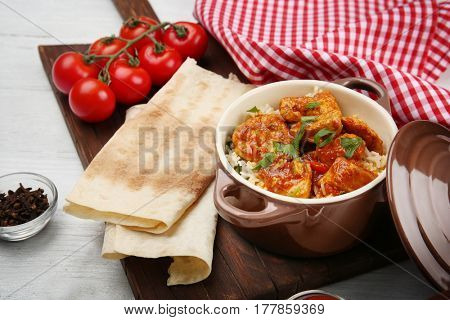 Saucepan with delicious chicken tikka masala and rice on table